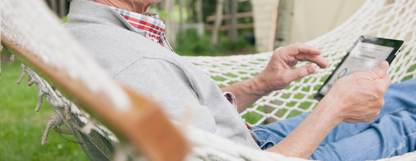 Person relaxing in hammock with tablet showing financial figures.