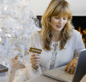 Woman shopping online for holiday gifts with a Christmas tree in the background