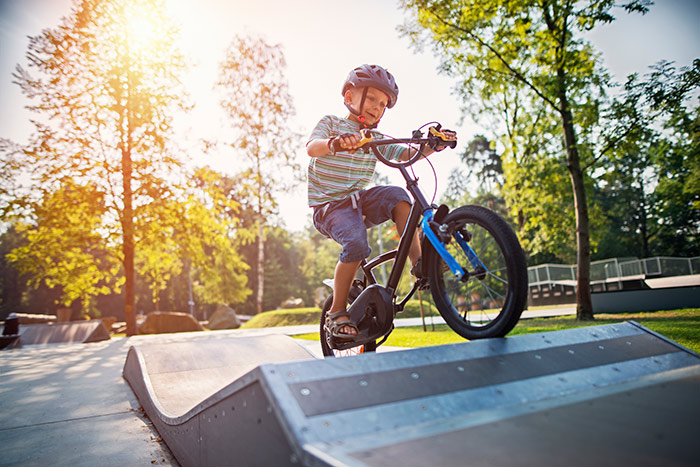 A child rides his bike over a ramp.