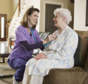 Nurse using stethoscope on elderly patient at home